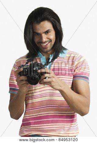 Photographer using a digital camera and smiling