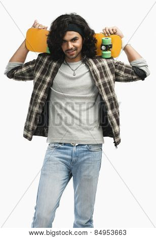 Man holding a skateboard on his shoulders