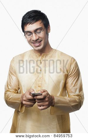 Bengali man text messaging on a mobile phone