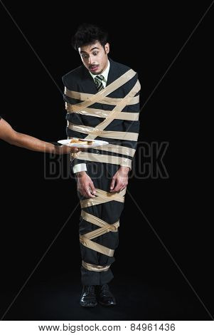 Businessman tied up with adhesive tape and looking to toast with greed