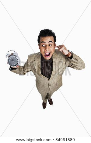 Businessman showing an alarm clock and looking irritated