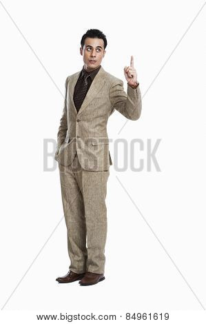 Businessman pointing with his hands in pockets