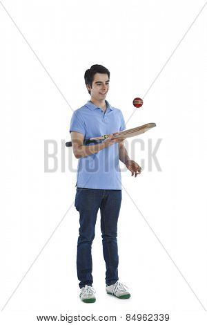 Man tossing a ball with a cricket bat