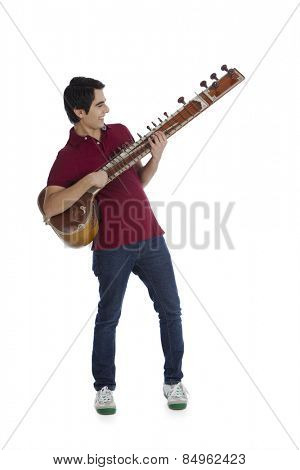 Man playing a sitar and smiling