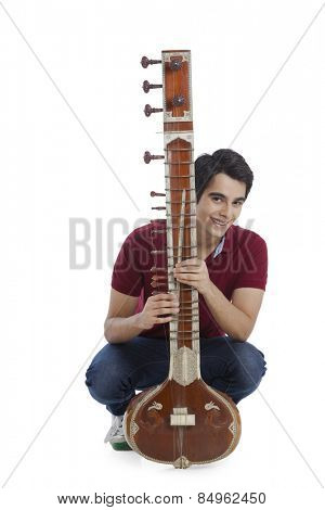 Portrait of a man playing a sitar and smiling