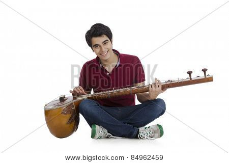 Happy man sitting on the floor and playing a sitar