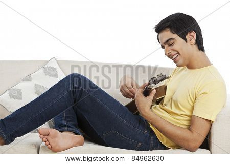 Man sitting on a couch and playing mandolin