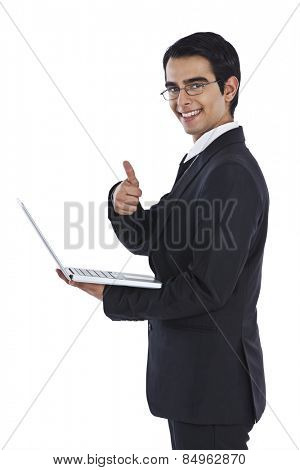 Portrait of a businessman using a laptop and showing thumbs up