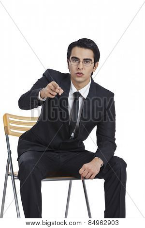 Portrait of a businessman sitting on a chair and pointing
