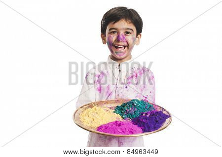 Boy holding Holi colors in a plate