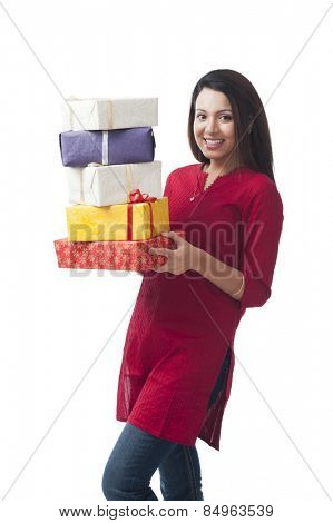 Portrait of a happy woman holding a stack of gifts
