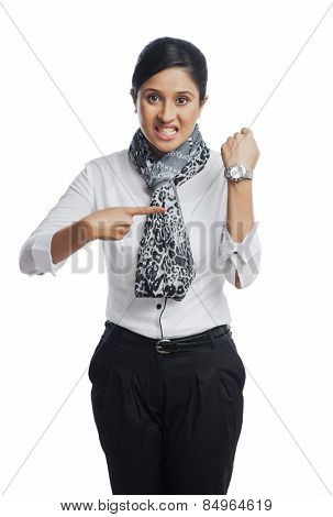 Businesswoman clenching teeth and pointing toward a wristwatch