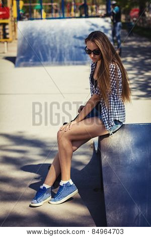 Cute Girl In Shorts With A Skateboard On The Playground
