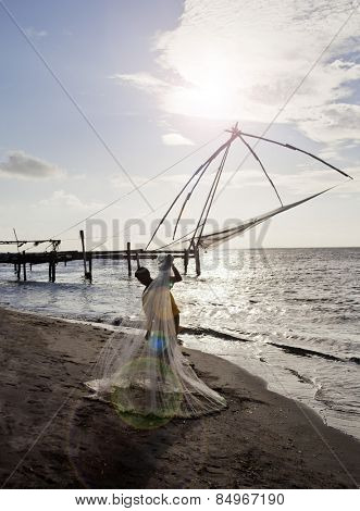 Fisherman holding a fishing net on the beach, Cochin, Kerala, India