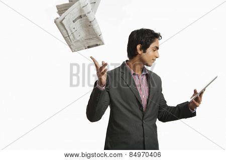 Businessman looking at a digital tablet and throwing newspaper