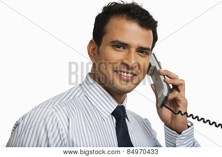 Businessman talking on a landline phone and smiling