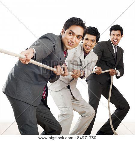 Three Businessmen playing tug-of-war