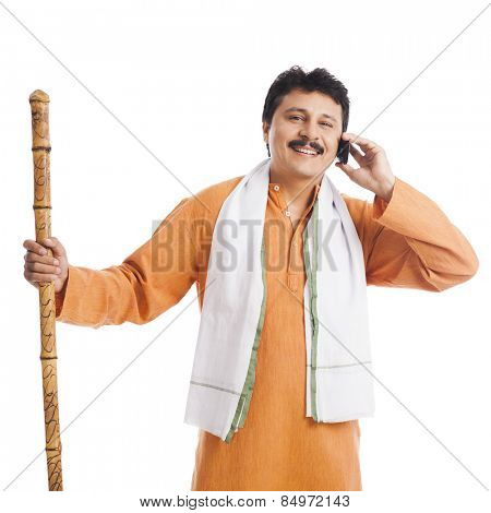 Portrait of a man holding a wooden staff and talking on a mobile phone