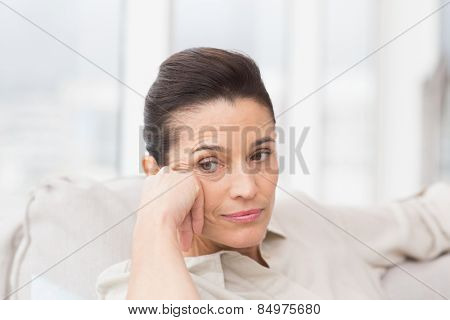 Thoughtful woman sitting on sofa in living room