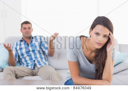 Portrait of woman suffering from headache while man quarreling at home