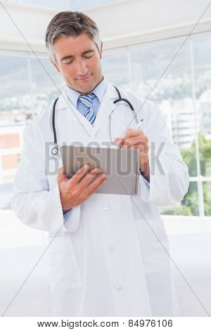 Doctor writing on clipboard in medical office