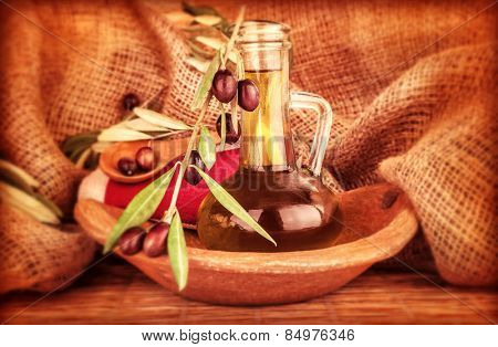 Extra virgin olive oil in the bottle decorated with fresh ripe olive branch on burlap background, beautiful food still life, healthy eating concept