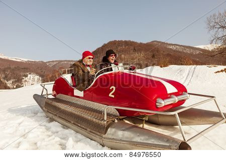 Elderly couple on a pedalo in the snow