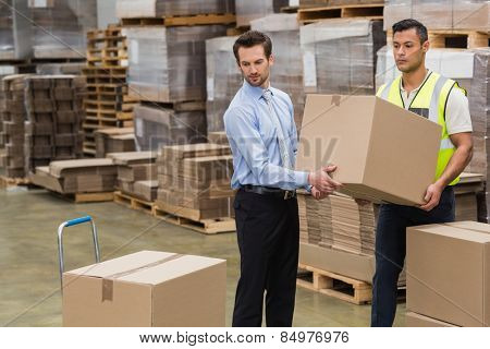 Warehouse worker and manager carrying a box together in a large warehouse
