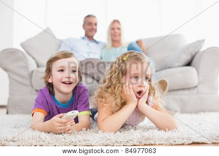 Surprised children watching TV while parents sitting on sofa at home