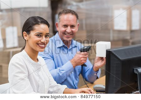 Manager scanning box while his colleague typing on laptop in a large warehouse