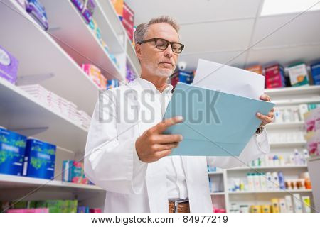 Concentrated pharmacist reading documents in the pharmacy