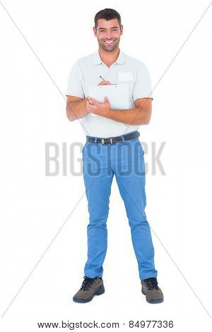 Full length portrait of confident male supervisor writing on clipboard over white background