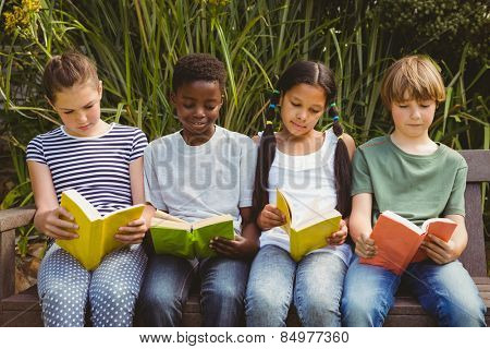 Portrait of children reading books at the park