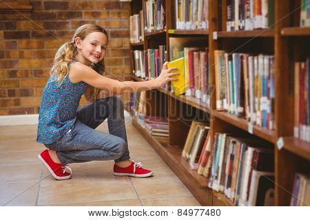 Side view of cute little girl selecting book in the library