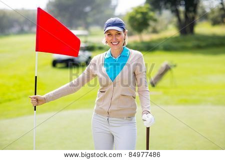 Female golfer smiling at camera and holding her golf club on a sunny day at the golf course