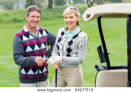 Happy golfing couple with golf buggy beside on a foggy day at the golf course