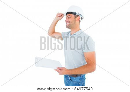 Smiling manual worker wearing hardhat while holding clipboard on white background