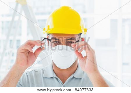 Confident handyman wearing protective eyewear at construction site