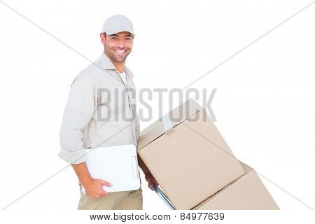 Portrait of happy delivery man pushing trolley of boxes on white background
