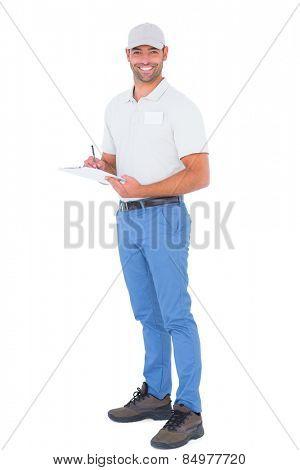 Full length portrait of confident male supervisor writing on clipboard over white background