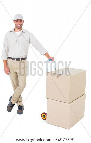 Full length portrait of confident delivery man with cardboard boxes on white background