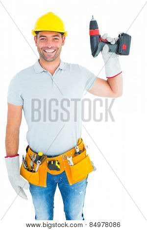 Portrait of handyman wearing tool belt while holding power drill on white background