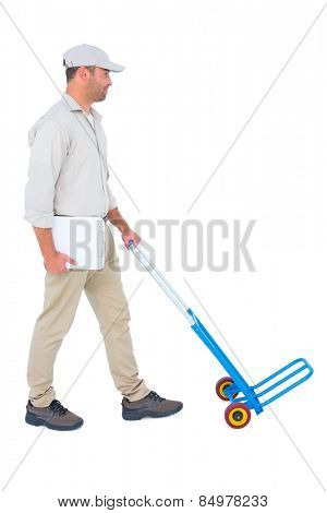 Full length of delivery man pushing empty trolley on white background