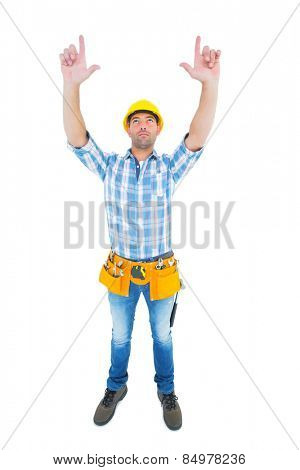 Full length of manual worker forming hand frame while looking up on white background