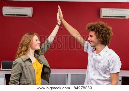 Casual young businessman and woman high fiving in office