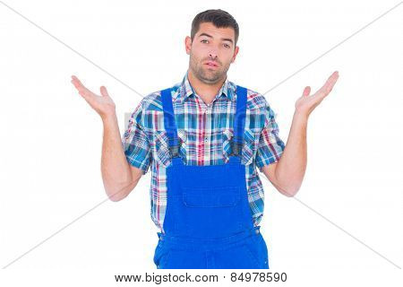 Portrait of confused handyman giving I dont know gesture on white background