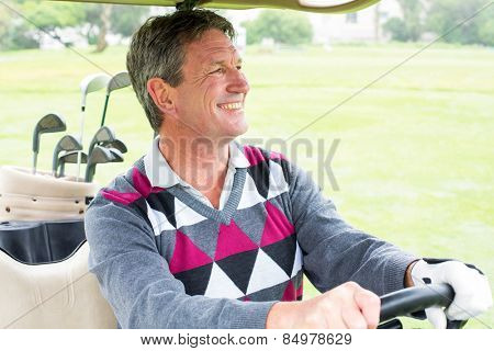 Happy golfer driving his golf buggy on a sunny day at the golf course