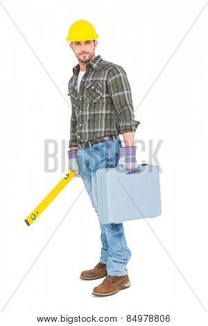 Full length portrait of manual worker with spirit level and toolbox on white background