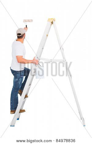 Handyman climbing ladder while using paint roller on white background