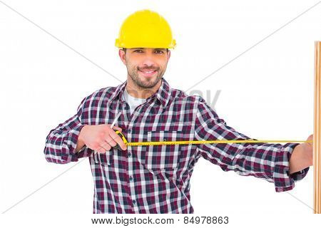 Handyman using measure tape on wooden plank on white background